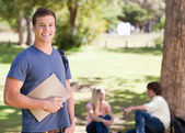 Portrait of a smiling student holding a textbook — Stock Photo