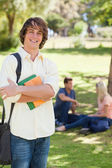 Smiling young man posing with textbook — Stock Photo