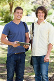 Portrait of two smiling male students with a touch pad — Stock Photo