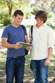 Two smiling male students with a touch pad — Stock Photo