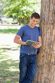 Male student leaning against a tree while using a touch pad — Stock Photo