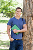 Portrait of a muscled student holding a textbook — Stock Photo
