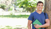 Portrait of a smiling muscled student holding a textbook — Stock Photo