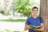 Portrait of a smiling toothy student holding a textbook — Stock Photo