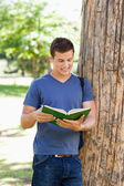 Muscled young man reading a book — Stock Photo