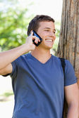 Close-up of a smiling young man on the phone — Stock Photo