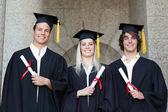Graduates holding their diploma while posing — Stock Photo