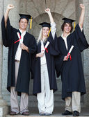 Smiling graduates raising arm — Stock Photo