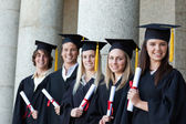 Graduates posing in single line — Stock Photo