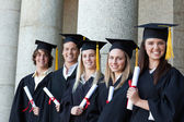 Smiling graduates posing in single line — Stock Photo