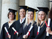 Retrato de sonrientes graduados posando en línea — Foto de Stock