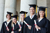Portrait of graduates posing in single line — Stock Photo