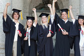 Smiling graduates posing while raising arms — Stock Photo