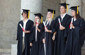 Smiling graduates posing while holding their diploma — Stock Photo