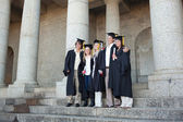 Five graduates posing while holding their diploma — Stock Photo