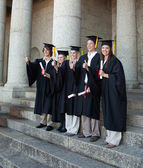 Laughing graduates posing the thumb-up — Stock Photo