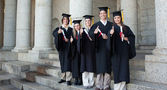 Five happy graduates posing the thumb-up — Stock Photo