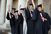 Five happy graduates posing the arm raised — Stock Photo