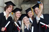 Primer plano de los graduados felices tomando una foto de sí mismos — Foto de Stock