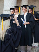 Blonde graduate taking a picture of her friend — Stock Photo