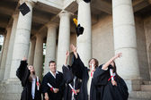 Graduates throwing their hats in the sky — Stock Photo