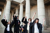Graduates dancing in togas — Stock Photo
