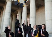 Happy graduates throwing their hats in the sky — Stock Photo