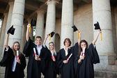 Graduados sosteniendo sus sombreros — Foto de Stock
