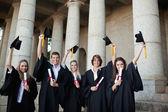 Graduates holding up their hats — Stock Photo