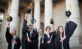 Smiling graduates holding up their hats — Stock Photo