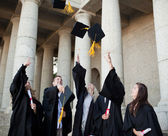 Smiling graduates throwing their hats in the sky — Stock Photo