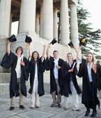 Five happy grad students raising their hats — Stock Photo