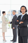 Young businessman standing upright in front of colleagues shakin — Stock Photo