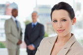 Young secretary standing in front of two executives in a relaxed — Stock Photo