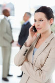 Businesswoman seriously talking on the phone with executives beh — Stok fotoğraf