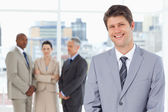 Young smiling manager standing upright with his team behind him — Stock Photo