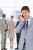 Homme d'affaires sérieuse, en utilisant un téléphone cellulaire, alors que son équipe est derrière — Photo