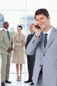 Homem de negócios usando um telefone celular na frente de sua equipe a sorrir — Foto Stock