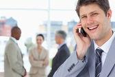 Jovem gerente rindo enquanto estiver usando seu telefone móvel — Foto Stock