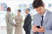 Młody menedżer poważne wysłać wiadomość tekstową za pomocą swojego telefonu komórkowego — Zdjęcie stockowe
