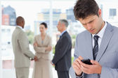 Young serious manager using his cell phone to send a text — Stockfoto