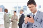 Jonge manager verzenden van een tekst met zijn mobiele telefoon in een concentr — Stockfoto