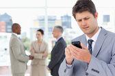 若いマネージャー、クロックで彼の携帯電話とテキストを送信します。 — ストック写真