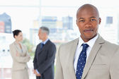 Young executive in a suit standing upright while his team is beh — Stock Photo