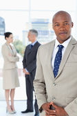Businessman wearing a suit and crossing his hands with his team — Stock Photo
