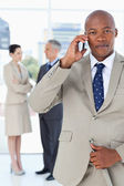 Young manager talking on the phone very seriously while his team — Stockfoto