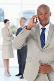 Młody menedżer rozmawia przez telefon bardzo poważnie, podczas gdy jego zespół — Zdjęcie stockowe