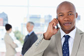 Serious businessman in a suit talking on the phone while his tea — Stock Photo
