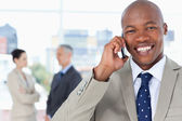 Young manager laughing while using his cell phone — Stock Photo