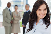Young executive woman smiling and looking ahead with the team in — Stock Photo